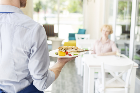 Midsection of waiter serving lunch to mature customer sitting at table in restaurant 写真素材