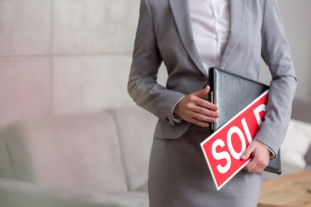 Midsection of young saleswoman holding sold placard and document in apartment