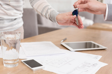 Hand of saleswoman giving house keys to female client over documents on table in apartment