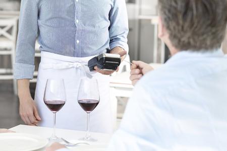 Mature customer paying through credit card at restaurant 写真素材