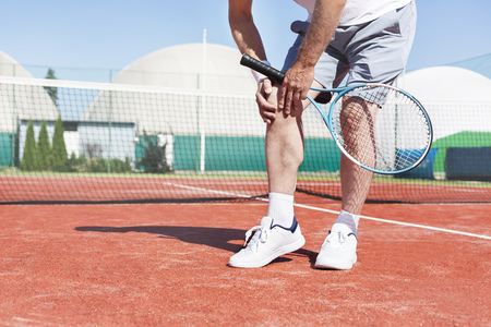 Low section of mature man holding tennis racket while suffering from knee pain on red tennis court during summer 写真素材