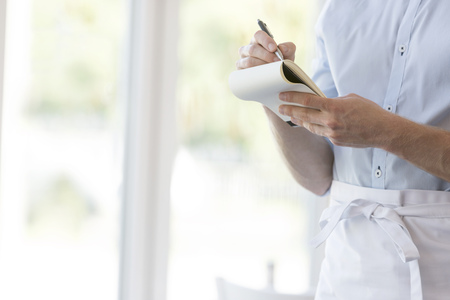 Midsection of young waiter writing on notepad while standing at restaurant