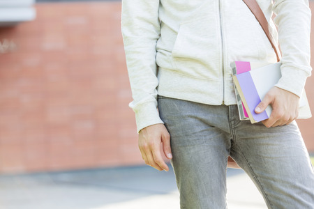Midsection of student holding books at campus 写真素材