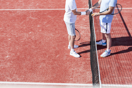 Low section of men shaking hands while standing by tennis net on red court during match 写真素材