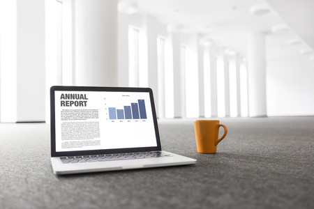 Annual report graph on laptop by coffee mug at new empty office