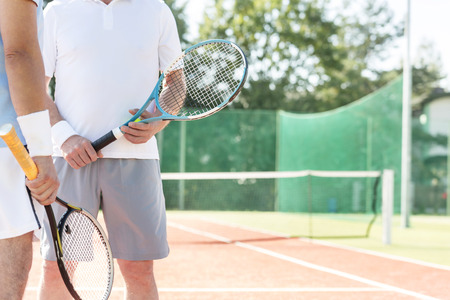 Midsection of mature men holding rackets while standing on tennis court during summer weekend