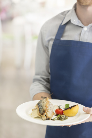 Midsection of young waiter serving lunch at restaurant