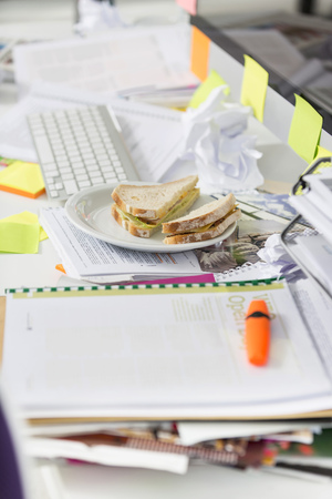 Closeup of sandwich and documents on desk in office Imagens