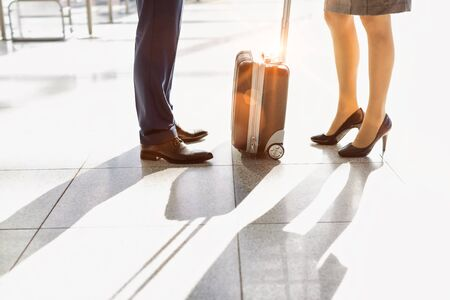 Cropped image of businessman and businesswoman standing in airport