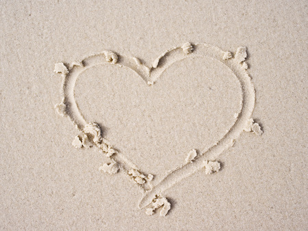 evoke: Heart drawn on sand.