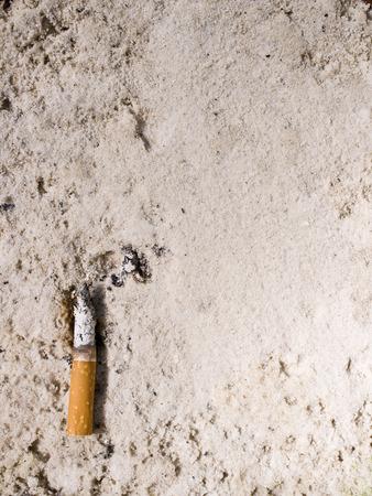 A cigarette in sand ashtray. photo