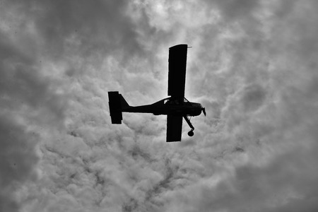 aerobatics: Old plane is flying in the sky. Black & white. Stock Photo