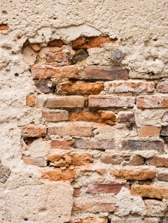 building structure: Old brick wall with cracked stucco layer. Stock Photo