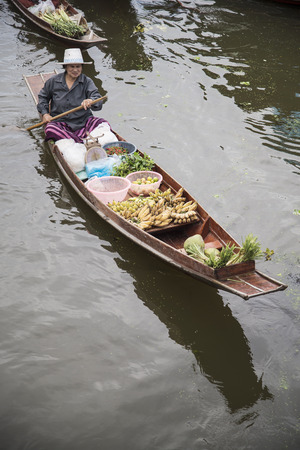 tha: RATCHABURI THAILAND -Oct 3: Wooden boats are loaded with fruits from the orchards at Tha kha floating market on October 3, 2015 in Ratchaburi,Thailand. A traditional way still practiced in Tha kha canals of Thailand.