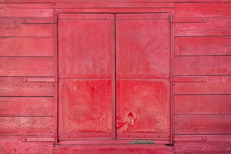 painted wood: Window of a classic red painted barn made of wood.