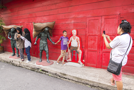 rice mill: SONGKLA, Thailand - OCT 24:  People shooting with street art at Hub Hoe Hin, Red rice mill plant, Significance fabrics of the old town at Songkla, Thailand. Editorial
