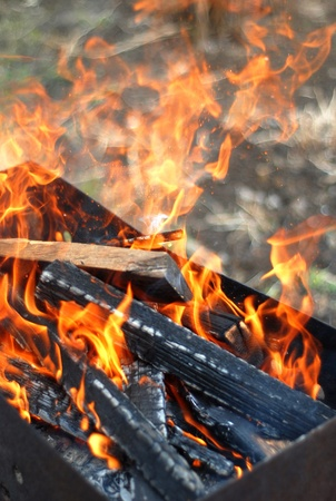 Red fire burning in a barbecue with wood planks Stock Photo