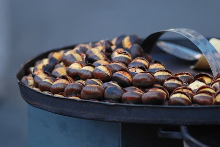 Roasted chestnuts on the iron tray outdoors Stock Photo