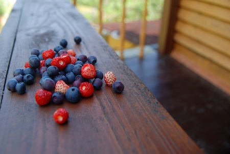 Fresh forest berries on the wooden balcony outdoors