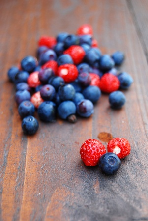 Delicious forest berries on wooden table. Shallow dof, vertical format