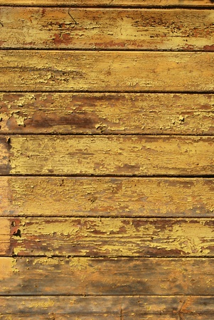 Old shabby painted yellow wooden planks texture