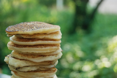 High pile of thick russian pancakes for breakfast. Natural light, green background