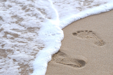 leading: Footprints in the sand leading to the sea Stock Photo