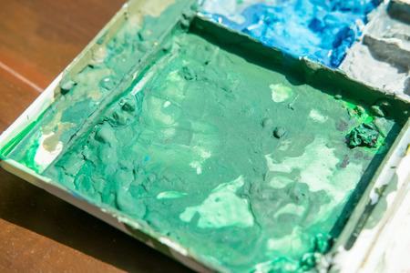 Watercolor paints box palette on wooden floor