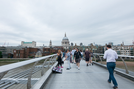 London, England - 28 July 2016 : Tourists walking across the Millennium Bridge, which is a steel suspension bridge for pedestrians crossing River Thames on 28 July 2016 in London, United Kingdom Editorial