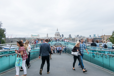 st  paul   s cathedral: London, England - 28 July 2016 : Tourists walking across the Millennium Bridge, which is a steel suspension bridge for pedestrians crossing River Thames on 28 July 2016 in London, United Kingdom Editorial