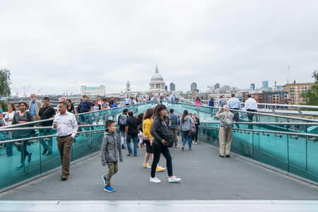 st pauls: London, England - 28 July 2016 : Tourists walking across the Millennium Bridge, which is a steel suspension bridge for pedestrians crossing River Thames on 28 July 2016 in London, United Kingdom Editorial