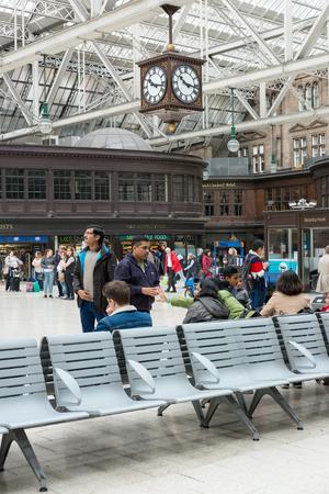 corner clock: Glasgow, Scotland - 17 September 2016 : Passengers waiting, sitting, walking around Glasgow Central Train Station in Glasgow, United Kingdom on 17 September 2016 Editorial