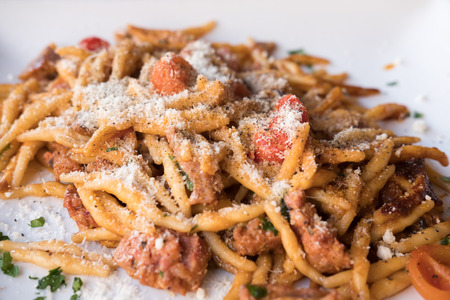 mediterranean culture: Pasta with Tomato sauce, Sprinkling Cheese. On plate in the restaurant. Stock Photo
