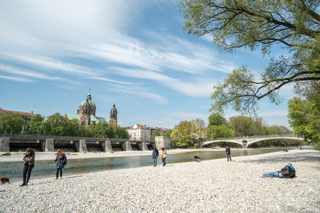 st: Munich, Germany - 21 April 2017 : View of people enjoy sunny day at the river bank of Isar river in Munich. WIth St Lukas Church on background. Editorial