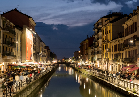 Milan, Italy - 16 September 2017: People walking around Naviglio Grande with building along the canal at night