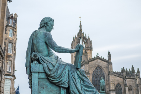 David Hume Statue with St. Giles Cathedral on the background on Royal Mile in Edinburgh, Scotland 写真素材