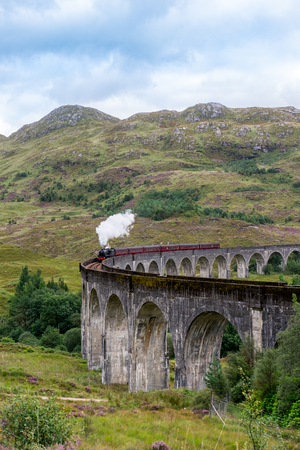 Jacobite Steam Train Locomotive passing Glenfinnan Viaduct, the famous location appears on the films