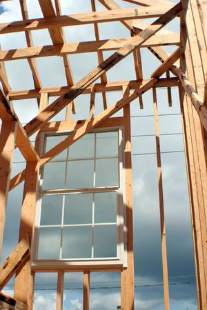 This is a new home under construction with a window installed while its still being framed Stock Photo