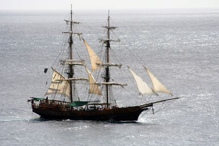 A close shot of a pirate ship that is out to sea and sailing away photo