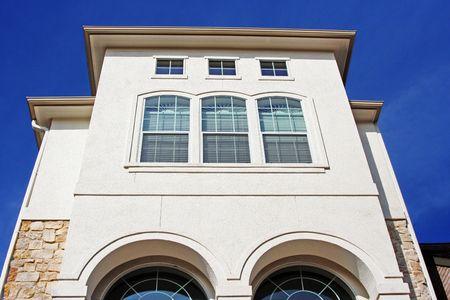 A modern stucco house that has a blue sky background