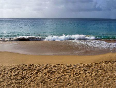 Die Wellen, die auf einem sandigen Strand vor einem Sturm zusammenstoßen, kommt herein Standard-Bild - 2775135