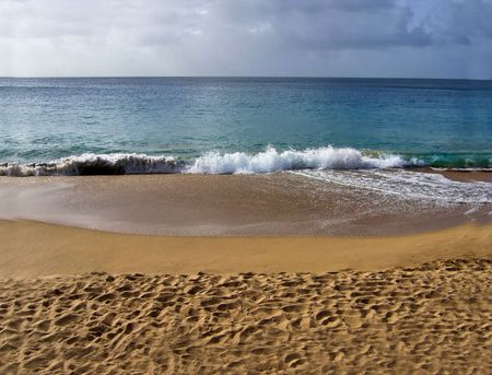 Waves crashing on a sandy beach before a storm comes in Stock Photo