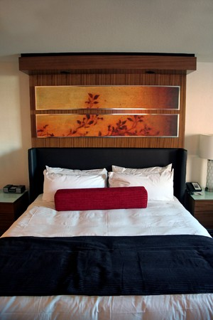 A hotel room bed with clean white sheets
