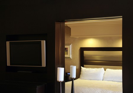 luxury hotel room: A hotel room dresser with a bed reflecting in the mirror