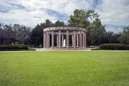 A classical monument with a single fountain behind a great lawn Stock Photo