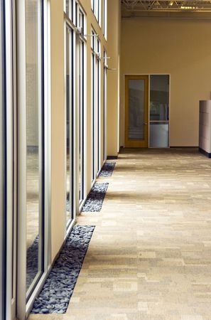 A office building hallway next to some large glass windows Stock Photo
