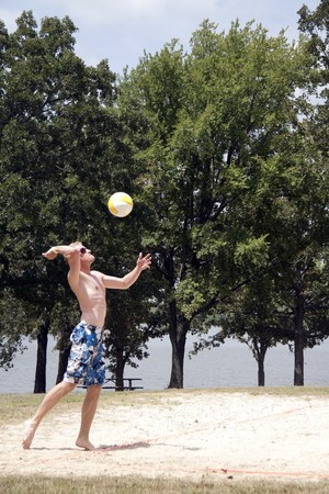 A man serving a volleyball on a beach court photo