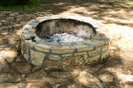 An empty stone fire pit with just ashes left Stock Photo