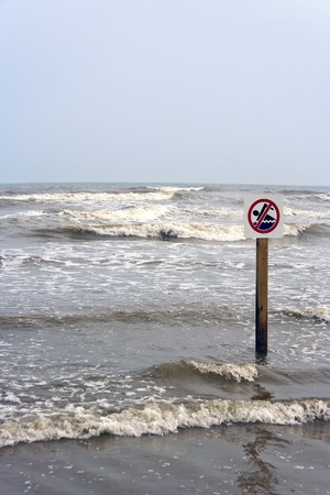 no swimming sign: A no swimming sign at the beach with rough surf
