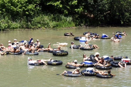 NEW BRAUNFELS, TX - MAY 2009: Several people flowing down the Guadalupe River known for its large increased visitor traffic for the summer time. Tubers where taken on May 30th, 2009 in New Braunfels, Texas.